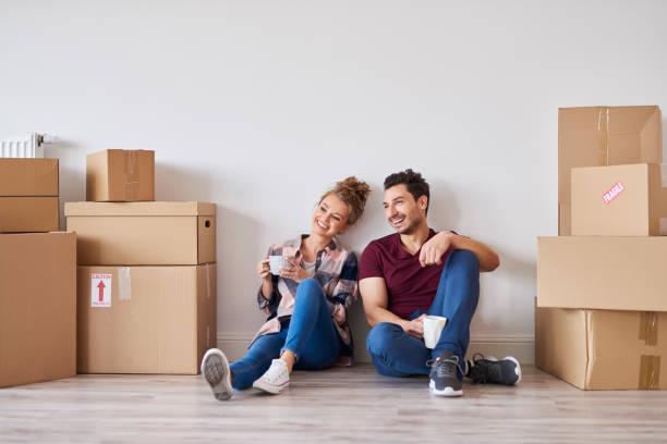 Glückliches Paar mit Kaffeetassen entspannen in ihrem neuen Zuhause – Foto