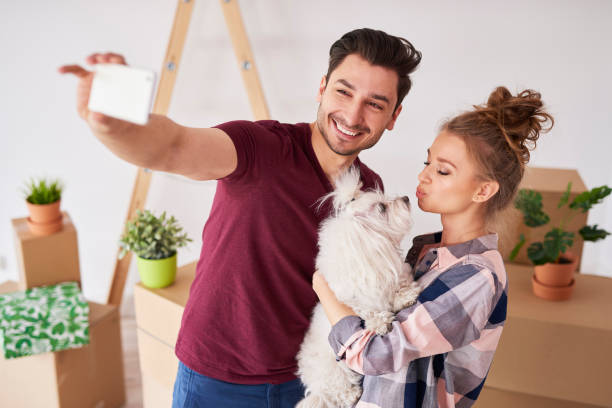 Happy couple with dog making a selfie in new home stock photo
