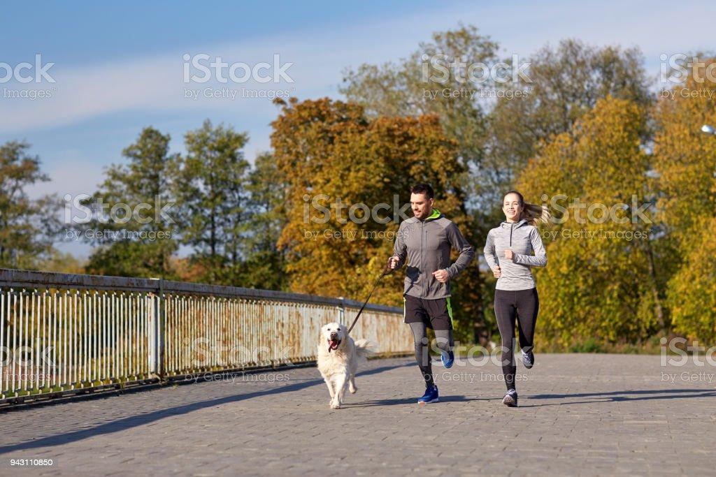 Glückliches Paar mit Hund Laufen im Freien – Foto