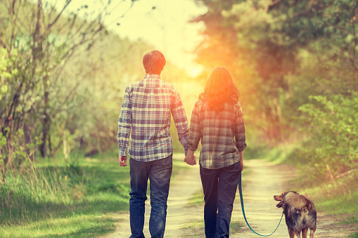 Happy couple with dog walking on rural road at sunset.
