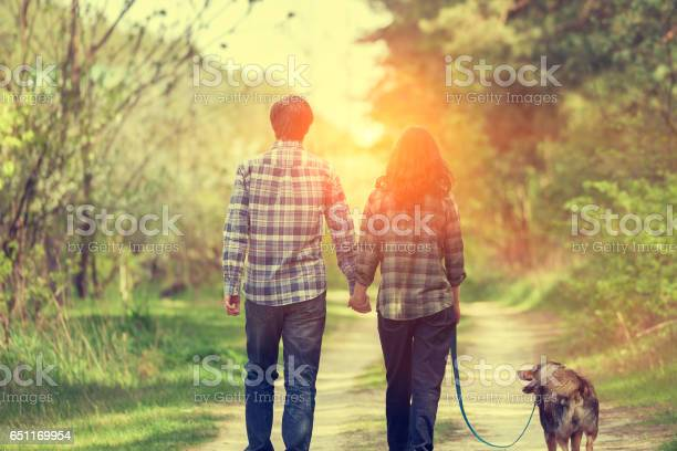 Happy couple with dog walking on rural road at sunset picture id651169954?b=1&k=6&m=651169954&s=612x612&h=yowctwncly 2iorotarvwff3icfy2gujgpsvqjcofdy=