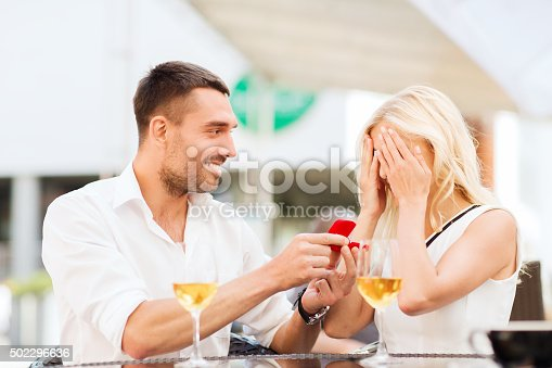 istock happy couple with engagement ring and wine at cafe 502296636