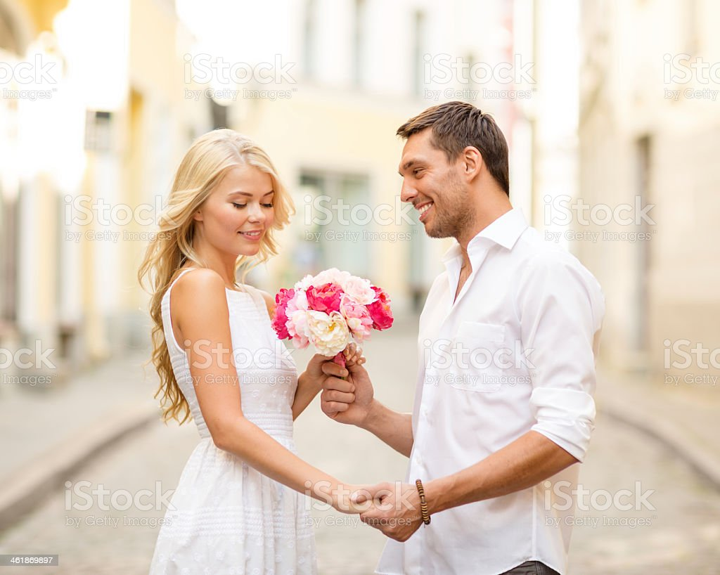 happy couple with flowers in city stock photo