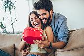 自宅で抱き合うギフトボックスを持つ幸せなカップル。