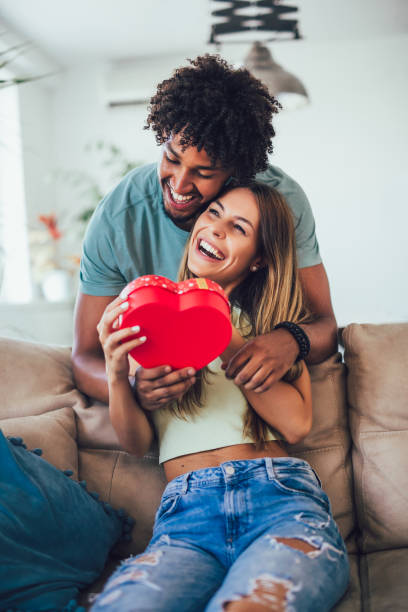 Happy couple with gift box hugging at home. stock photo