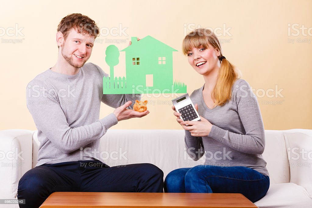 Happy couple with house and calculator. foto royalty-free
