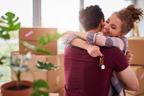 glückliches paar mit schlüsseln der neuen wohnung - eigenheim stock-fotos und bilder