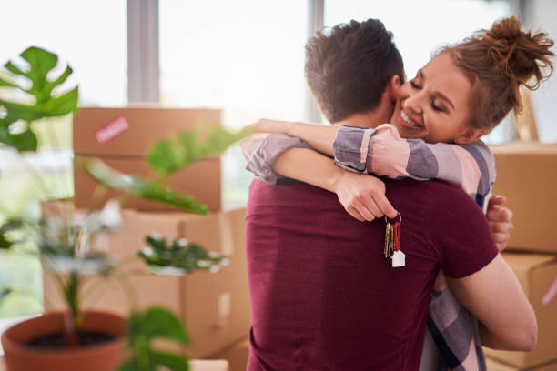Happy couple with keys of new apartment stock photo