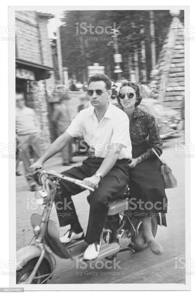 Happy couple with motorcycle in 1950 royalty-free stock photo