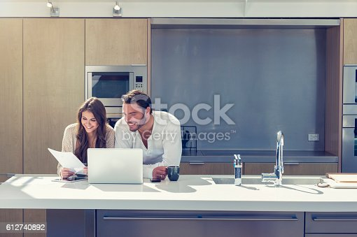 Happy couple with paperwork. They are standing at the kitchen bench working online with a computer and bills. They have coffee. Copy space