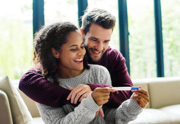happy couple with pregnancy news - family planning stock photos and pictures