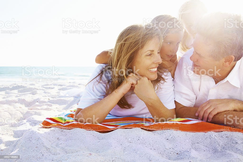 Happy couple with their cute daughter lying on blanket royalty-free stock photo