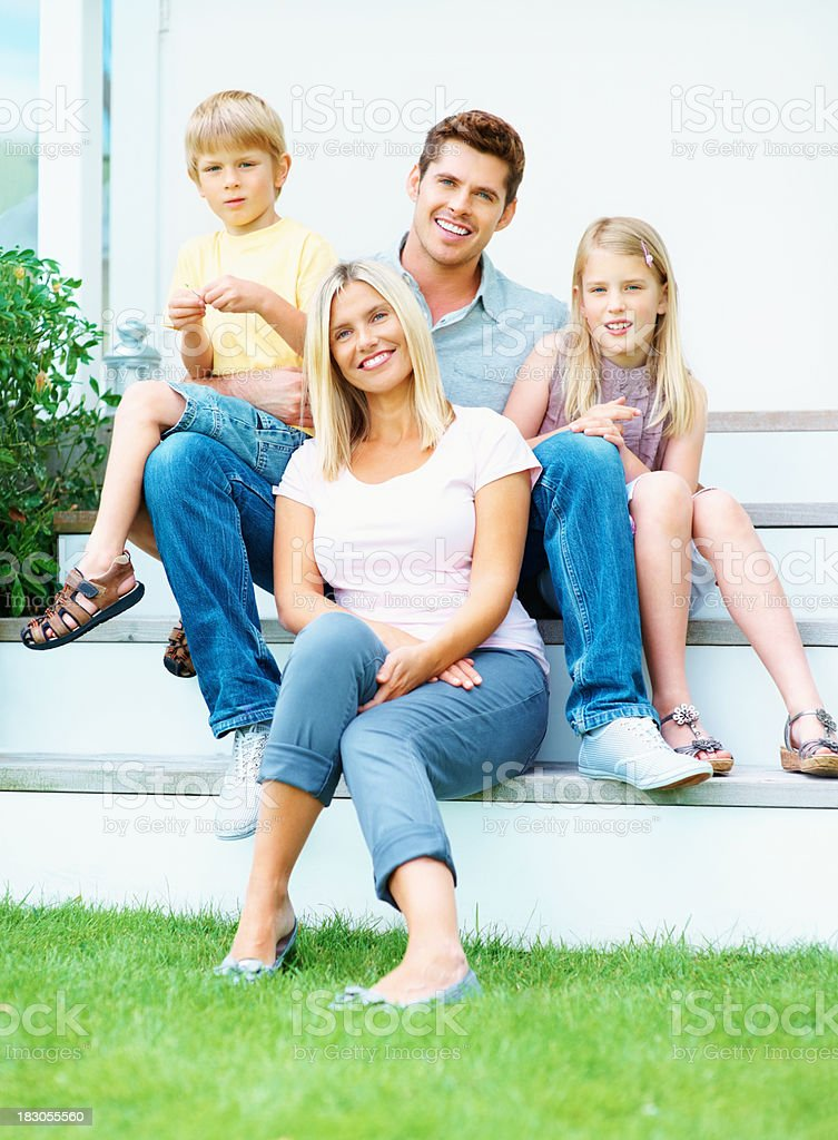 Happy couple with their kids relaxing on stairs by lawn royalty-free stock photo