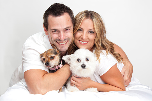 Happy couple with two cute pet dogs hugging.