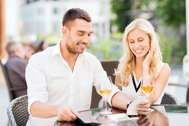 coppia felice con il portafogli e bill al ristorante - holiday and invoice family foto e immagini stock