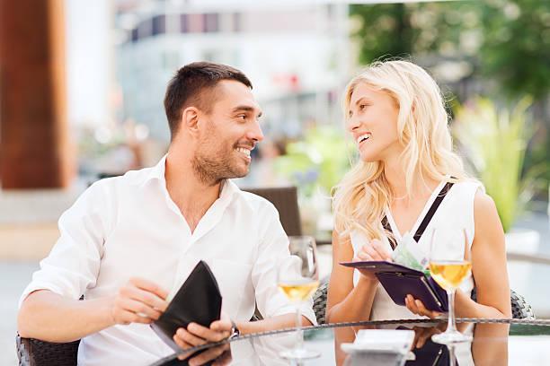 glückliches paar mit geldbörse zahlenden rechnung im restaurant - eurozahlen stock-fotos und bilder