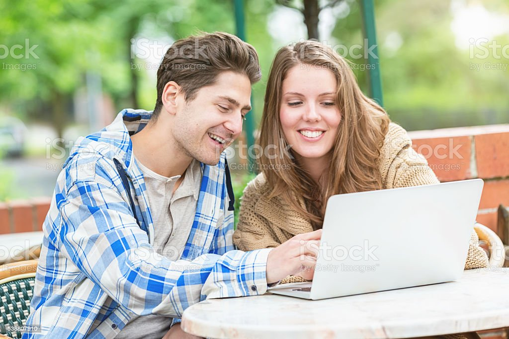 Happy couple writing blog in street cafe stock photo