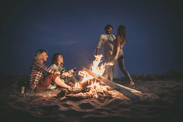 glückliche paare, die sich bei einer nächtlichen party am strand am lagerfeuer vergnügen. - tanz camp stock-fotos und bilder