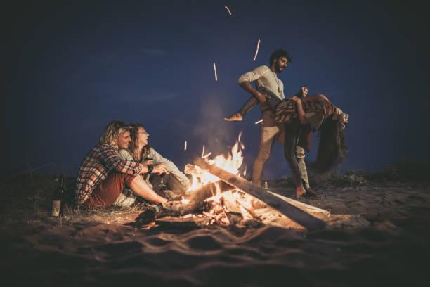 glückliche paare, die sich auf einer nachtparty am strand am lagerfeuer amüsieren. - tanz camp stock-fotos und bilder