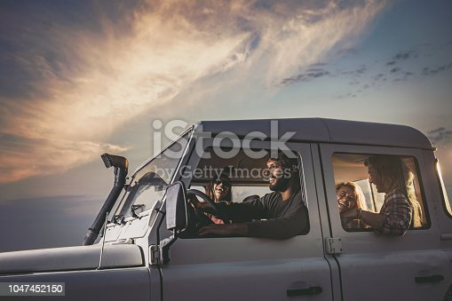 Young happy couples having fun while going on a road trip by truck. Copy space.