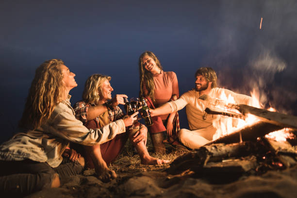 happy couples toasting with alcohol by the campfire at night. - falò spiaggia foto e immagini stock
