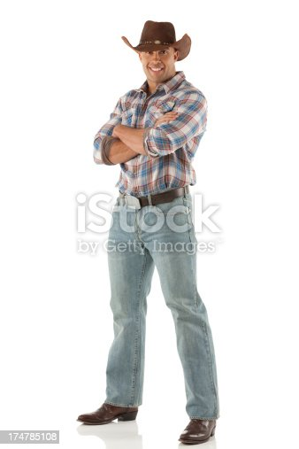 Happy cowboy standing with his arms crossed