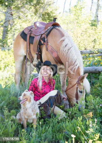 Happy cowgirl relaxes with her horse and dog.