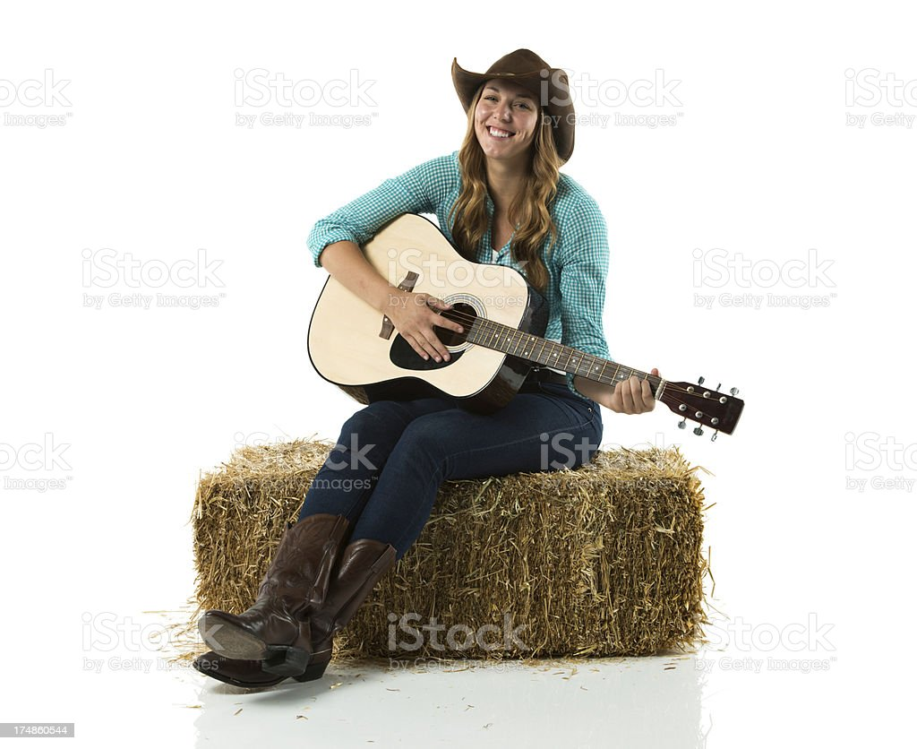 Happy cowgirl sitting on hay stack with guitar royalty-free stock photo