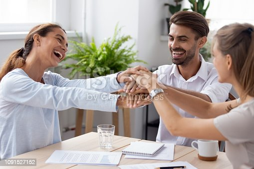 istock Happy coworkers getting reward feels happy stacked their hands together 1091527152