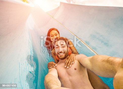 Happy crazy couple taking selfie photo with action camera in aqua park - Young people having fun in summer holidays with technology trends - Vacation, youth, love and travel concept - Focus on faces
