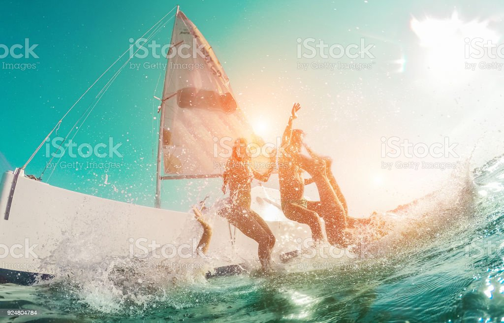Happy crazy friends diving from sailing boat into the sea - Young people jumping inside ocean in summer vacation - Main focus on center man - Travel and fun concept - Fisheye lens distortion - fotografia de stock