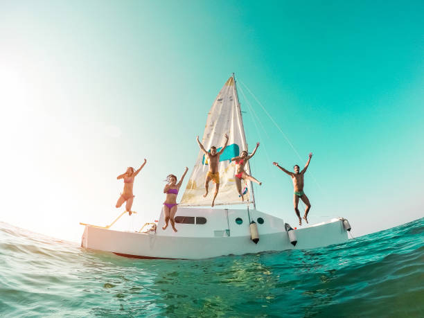 Happy crazy friends diving from sailing boat into the sea - Young people jumping inside ocean in summer vacation - Main focus on center guys - Travel and fun concept - Fisheye lens distortion - fotografia de stock
