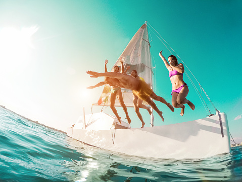 Happy crazy friends diving from sailing boat into the sea - Young people jumping inside ocean in summer vacation - Main focus on right girl body - Travel and fun concept - Fisheye lens distortion