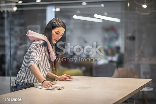 Smiling freelance worker cleaning the desk in the office. The view is through glass.