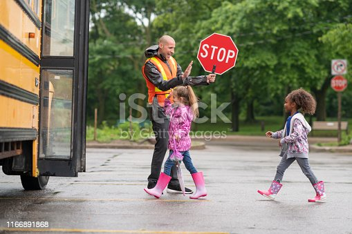 A male school bus driver is assisting a multi-ethnic group of students getting on the bus. The man is holding a stop sign and is wearing a reflective vest. He is happy to help keep the kids safe. He is giving the elementary students high fives as they board the bus in a single file line.