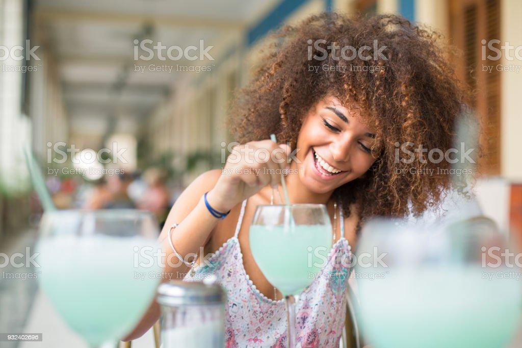 Happy Cuban girl drinking a cocktail in Havana bar stock photo