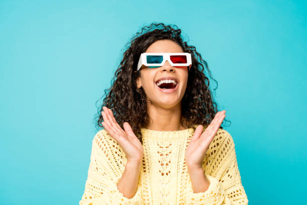happy curly african american woman laughing and gesturing in 3d glasses isolated on blue happy curly african american woman laughing and gesturing in 3d glasses isolated on blue 3 d glasses stock pictures, royalty-free photos & images