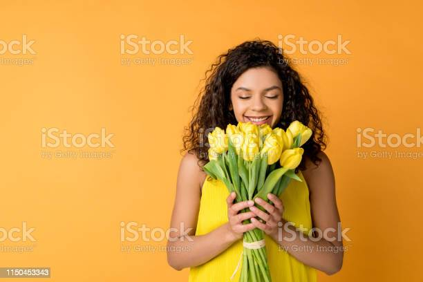 Photo of happy curly african american woman smelling yellow tulips isolated on orange