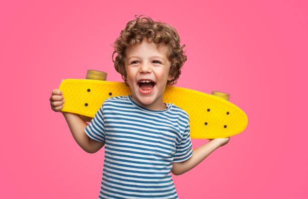 愉快的捲曲的男孩笑著拿著滑板 - 兒童 個照片及圖片檔