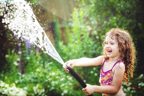 Glückliches lockiges Mädchen unter Wasser spritzt im Sommergarten. – Foto