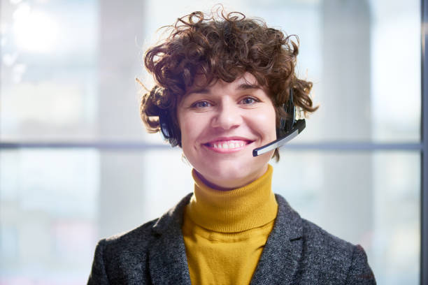 Happy curly woman working in call center stock photo