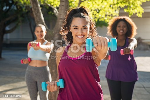 Portrait of young curvy woman with friends exercising with dumbbells. Group of three multiethnic girls working out in park during sunset. Smiling women in sportswear using dumbbell to lose weight.