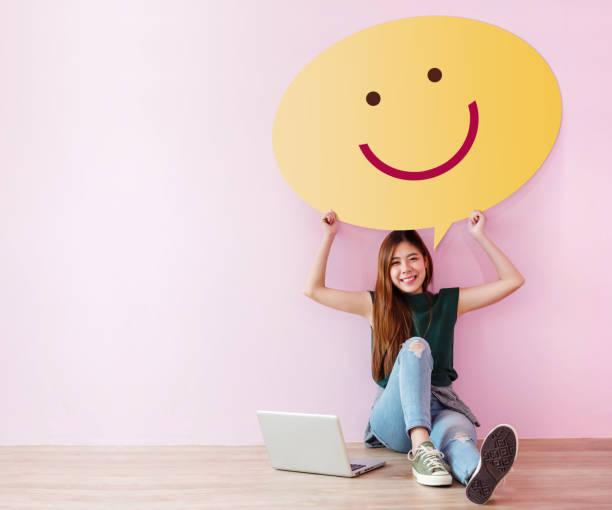 zufriedener kunde konzept. bewertung und feedback ihrer erfahrung für zufriedenheit umfrage online. young female in fröhliche haltung aufrichten sprechblase mit smiley-gesicht. sitzen sie auf dem boden mit laptop - kundenzufriedenheit stock-fotos und bilder
