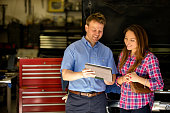 istock Happy customer discusses repairs with auto mechanic. Digital tablet. 471191754