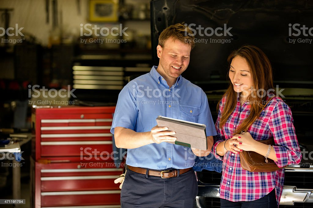 Happy customer discusses repairs with auto mechanic. Digital tablet. stock photo
