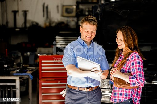istock Happy customer discusses repairs with auto mechanic in repair shop. 601948602