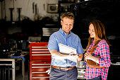 istock Happy customer discusses repairs with auto mechanic in repair shop. 601948602