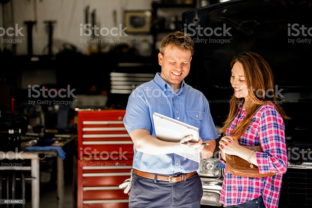 Happy customer discusses repairs with auto mechanic in repair shop. - foto stock