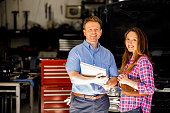istock Happy customer discusses repairs with auto mechanic in repair shop. 602289140