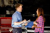 istock Happy customer discusses repairs with auto mechanic in repair shop. 602294986
